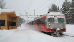 Commuter train passing station in snow weather Stock Footage