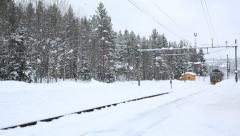 Freight train passing station in snow weather Stock Footage