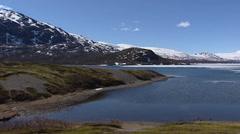 Mountain lake in spring, melting snow + pan peaks Jotunheimen National park Stock Footage
