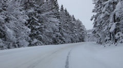 Driving on a country lane through snow-covered forest towards a village Stock Footage