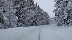 Ajaminen maa kaistaa läpi lumisen metsän kohti kylä Arkistovideo