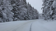Stock Video Footage of Driving on a country lane through snow-covered forest towards a village