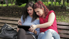 Lesbian. Two happy friends using tablet pc at park - stock footage