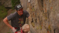 A rock climber attaches a carabiner as he scales a rock wall. - stock footage