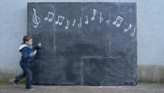 Little Multi-Ethnic Boy Skips/Hops Beneath Chalkboard Musical Notes Stock Footage