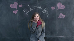 """Cute Girl Blows Kiss In Front Of """"I Love You"""" Written On A Chalkboard Stock Footage"""