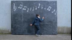Little Boy Pretends To Copy Musical Notes On A Chalkboard Stock Footage