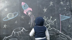 Cute Boy With A Chalkboard Drawing of Space Stock Footage