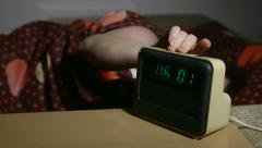 Woman waking up and stopping alarm clock - stock footage