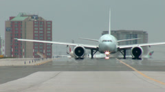Boeing 777 Airplane Taxiing, and a CRJ taxis in front Stock Footage