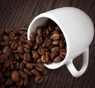 coffee cup full of roasted coffee beans. - stock photo