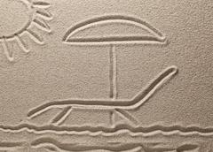 Drawing on sand. the sun shines on a chaise lounge with an umbrella Stock Photos