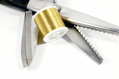 Pinking shears scissors and reel of gold thread Stock Photos
