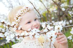 smiling toddler girl with brunches of apricot flowers - stock photo