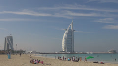 Burj Al Arab icon hotel public beach Jumeirah people enjoy Dubai sea sunny day Stock Footage