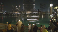 People relax Burj Khalifa lake Dubai fountain illuminated promenade building  Stock Footage