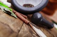 Stock Photo of tree spoons with spices and a bundle of herbs, mortar and pestle