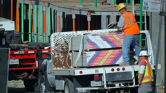 Workers unload drywall from the tuck at construction site - stock footage