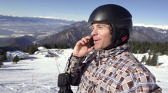 Skier Makes Telephone Call On The Snowy Slope Stock Footage