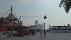 People passing creek park promenade pedestrian walking sunny day blue sky Dubai Stock Footage