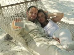 Couple on beautiful tropical beach taking photo of themselfs with cellphone NTSC - stock footage