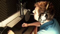 Voiceover artist recording in vocal booth studio Stock Footage