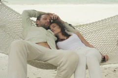 Young couple sleeping on hammock on the beach NTSC - stock footage
