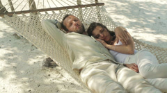 Young couple sleeping on hammock on the beach HD - stock footage