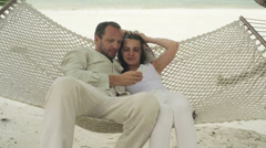 Couple with smartphone sitting on hammock on exotic beach HD Stock Footage