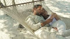 Couple with smartphone sitting on hammock on exotic beach HD - stock footage
