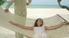 Woman relaxing on hammock on exotic beach HD - stock footage