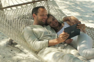 Stock Video Footage of Couple on hammock watching funny movie on tablet computer NTSC