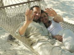 Happy young couple on hammock waving hands to camera NTSC - stock footage