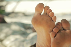 Man lying on hammock on exotic beach, focus on his feet NTSC - stock footage