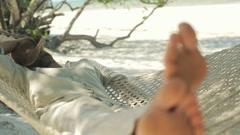 Young man sleeping on hammock on tropical beach HD Stock Footage