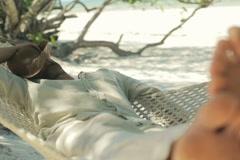 Young man sleeping on hammock on tropical beach NTSC Stock Footage