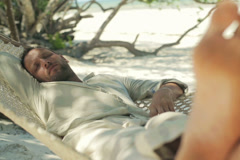 Young man sleeping on hammock on tropical beach NTSC - stock footage