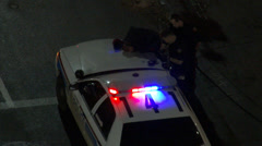 Man handcuffed on police cruiser hood Stock Footage