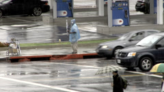 Homeless man selling umbrellas street corner Los Angeles - stock footage