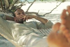 Young man lying on hammock and smoking cigarette NTSC Stock Footage