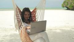 Woman with modern laptop sitting on hammock on exotic beach HD - stock footage