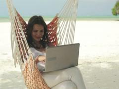 Woman with modern laptop sitting on hammock on exotic beach NTSC - stock footage