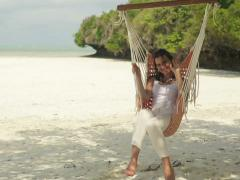 Beautiful woman waving to camera while relaxing on hammock NTSC Stock Footage