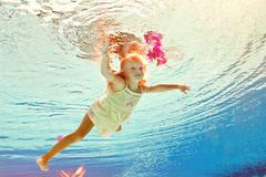 Girl in the swimming-pool under water with a flower Stock Photos