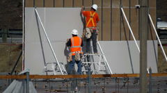 Construction workers install dry wall on metal wall frame at development site Stock Footage