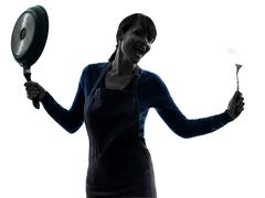 Woman happy cooking holding frying pan silhouette Stock Photos