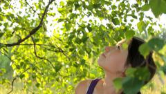 Girl watching sky through high trees tops in the rural landscape Stock Footage