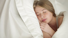 Pretty blonde girl sleeping in bed pulling up blanket and smiling in her slee - stock footage