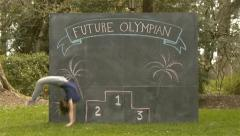 "Cute Girl Does Back Flip In Front Of Chalkboard with ""Future Olympian"" & Podium Stock Footage"