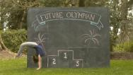 "Stock Video Footage of Cute Girl Does Back Flip In Front Of Chalkboard with ""Future Olympian"" & Podium"
